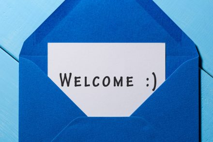 Welcome inscription. Hand drawn letter in blue envelope